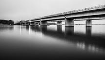 A long concrete bridge over a calm lake.