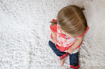 toddler girl sitting on a bed