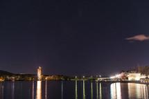 lights reflecting on lake water at night