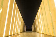 A long hallway with yellow walls and a black ceiling.