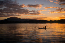 A boat is rowed in a river lit by the sunset.