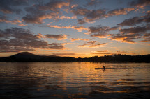A person rowing along a river while the sun sets.