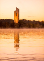 tower across a lake at sunset