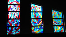 A set of three stained glass windows light a darkened corner of a church sanctuary with beautifully colored stained glass windows with red, blue, navy blue, gold, yellow, purple, violet and white stained glass colors to bring light to the dark corners of the world and add to the worship experience at local churches and chapels.