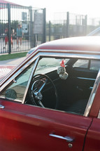 fuzzy dice hanging in a vintage red car