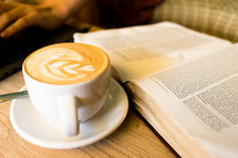 heart shaped creamer in a latte and open Bible