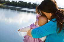 mom hugging baby daughter by a lake