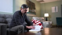 Mature man praying with open Bible next to an American flag on a couch
