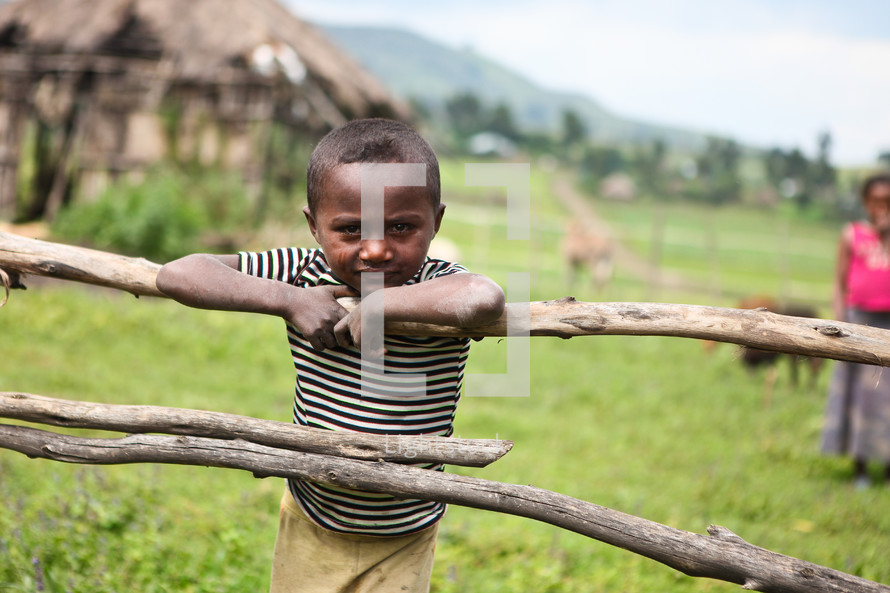 Young boy leaning on wooden fence