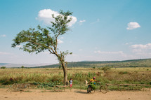 man with bananas on a bicycle on a dirt road