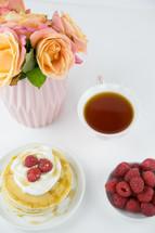 raspberries on pancakes and tea