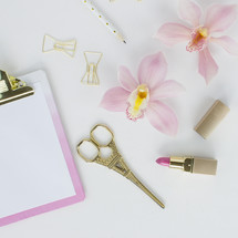 lipstick, clipboard, scissors, orchid, paper clips, and pencil