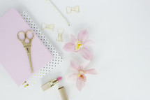 lipstick, clipboard, scissors, orchid, paper clips, gold, pink, Eiffel tower, pencil, feminine, desk, white background