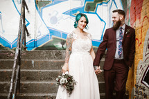 bride and groom in front of a graffiti covered wall