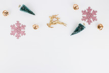 pink and gold Christmas ornaments and bottle brush Christmas trees on white