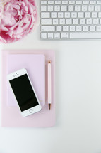 iPhone, pen, journal, computer keyboard, and pink peony on a white background