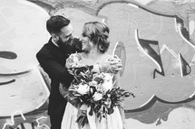 bride and groom hugging in front of a graffiti covered wall