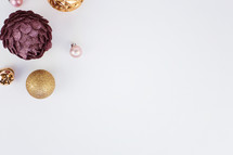 pink, purple, and gold Christmas ornaments on white