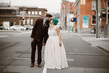 bride and groom in the middle of a street kissing