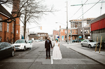 bride and groom standing in the middle of a downtown street