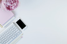 computer keyboard, iPhone, pen, journal, and pink peony on a white background