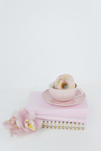 coffee and donuts on a stack of pink notebooks