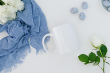 white roses, blue scarf, speckled blue eggs, white background, coffee mug