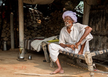 a man sitting on a cot in India