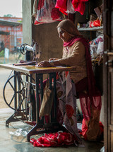 a woman in India sewing fabrics on a sewing machine