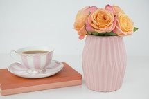 tea cup, book, and roses in a vase