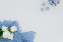 speckled blue eggs, blue scarf, and white roses
