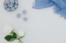 white roses, blue scarf, speckled blue eggs, white background