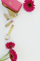 fuchsia gerber daisies, lipstick, gold watch, clutch, and cellphone