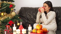 young girl with a cup of hot tea relaxing near Christmas tree.