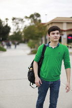 A young man walking down a sidewalk with a backpack.