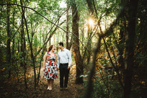 a happy couple standing in the woods