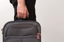 man ready for traveling carrying a carry-on suitcase