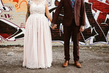 a bride and groom standing in front of a graffiti covered wall