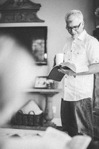 man standing holding a coffee cup and reading a Bible
