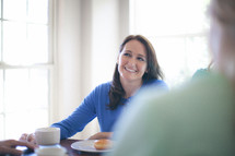 Smiling woman at the breakfast table.