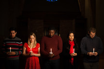 parishioners with bowed heads holding candles at a Candlelight Service