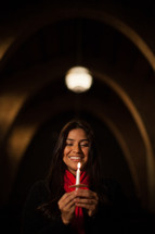 a woman holding a candle at a Christmas Eve service