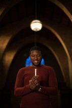 an African American man holding a candle at a Christmas Eve Service