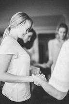 women holding hands in prayer