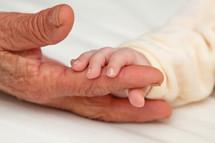 Infant holding grandmother's finger.