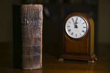 old leather Bible and clock on a table