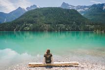 A woman sits on a log at the edge of a lake surrounded by mountains.
