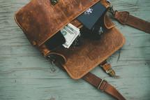 cash, cellphone, passport, camera in a messenger bag