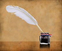 A feather quill pen dipped in an inkwell.