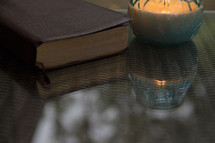 candle and Bible on a glass table top